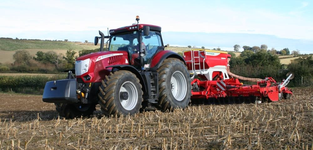 This images shows the McCormick X8 VT-Drive at work with a Pottinger seed drill